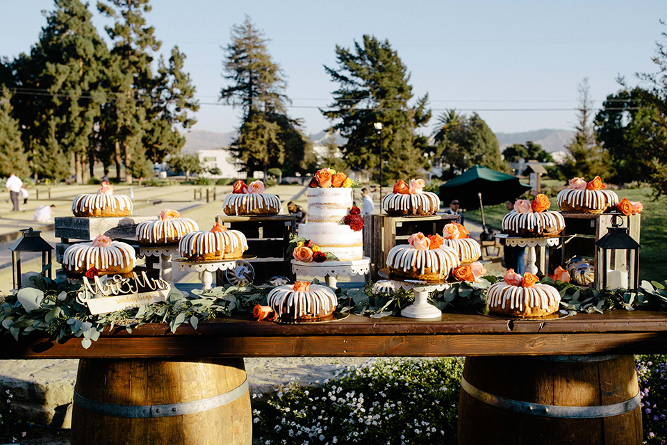 San diego autumn inspired outdoor wedding at limoneira ranch table set up light blue table linen with light orange and green flower centerpiece decor with light brown wooden rustic chairs and lantern and candle decor with wood dessert table and assorted cakes and dessert
