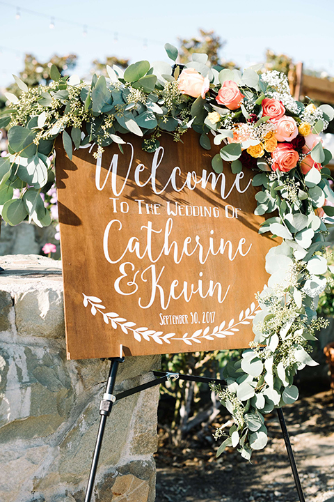 San diego autumn inspired outdoor wedding at limoneira ranch wedding welcome sign light brown wood rustic sign with white calligraphy writing for bride and groom with greenery floral decor on top standing on top of easel wedding photo idea for welcome sign