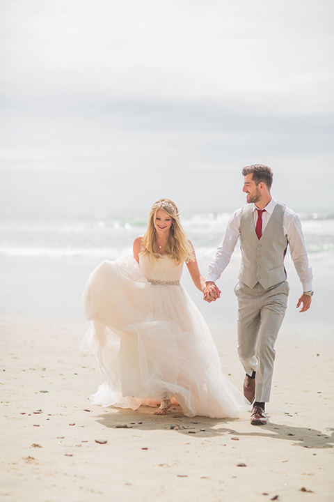 San diego beach wedding at blacks beach bride strapless ball gown with a sweetheart neckline and crystal belt and headband with groom light grey peak lapel suit by ike behar with a matching vest and white dress shirt with a long red matte tie and red flower lapel pin running and holding hands