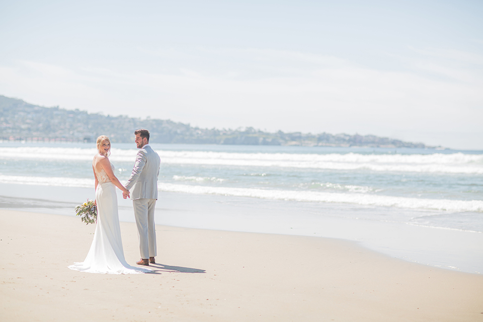 San diego beach wedding at blacks beach bride strapless ball gown with a sweetheart neckline and crystal belt and headband with groom light grey peak lapel suit by ike behar with a matching vest and white dress shirt with a long red matte tie and red flower lapel pin standing on the beach far away holding hands