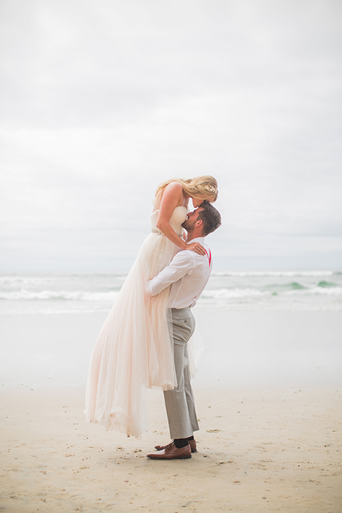 San diego beach wedding at blacks beach bride strapless ball gown with a sweetheart neckline and crystal belt and headband with groom light grey peak lapel suit by ike behar with a matching vest and white dress shirt with a long red matte tie and red flower lapel pin groom lifting bride touching heads and hugging