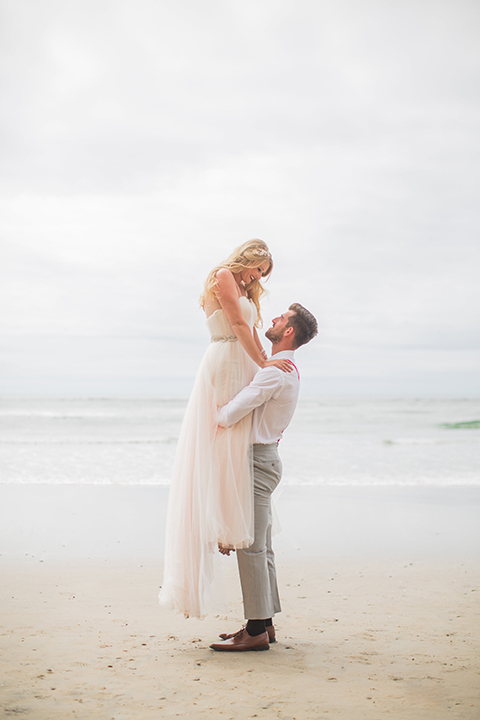 San diego beach wedding at blacks beach bride strapless ball gown with a sweetheart neckline and crystal belt and headband with groom light grey peak lapel suit by ike behar with a matching vest and white dress shirt with a long red matte tie and red flower lapel pin groom lifting bride smiling