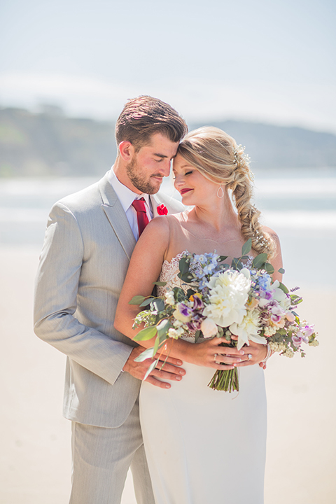 San diego beach wedding at blacks beach bride strapless ball gown with a sweetheart neckline and crystal belt and headband with groom light grey peak lapel suit by ike behar with a matching vest and white dress shirt with a long red matte tie and red flower lapel pin hugging and bride holding pink and blue floral bridal bouquet