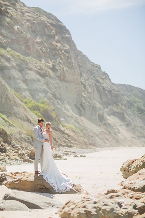 San diego beach wedding at blacks beach bride strapless ball gown with a sweetheart neckline and crystal belt and headband with groom light grey peak lapel suit by ike behar with a matching vest and white dress shirt with a long red matte tie and red flower lapel pin standing on the rocks on the beach hugging far away