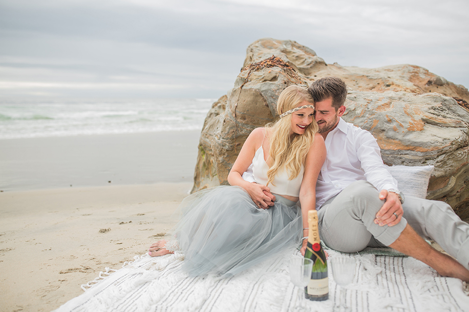 San diego beach wedding at blacks beach bride white top with light dusty blue tulle skirt and headband with groom light grey suit by ike behar with a white dress shirt and no tie sitting on blanket on the beach with bottle of champagne hugging