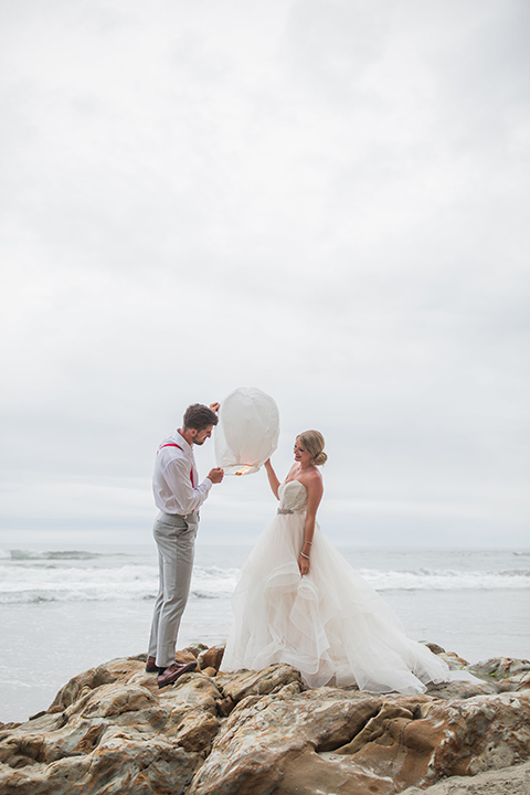 San diego beach wedding at blacks beach bride strapless ball gown with a sweetheart neckline and crystal belt and headband with groom light grey peak lapel suit by ike behar with a matching vest and white dress shirt with a long red matte tie and red flower lapel pin standing on the rocks holding white lantern