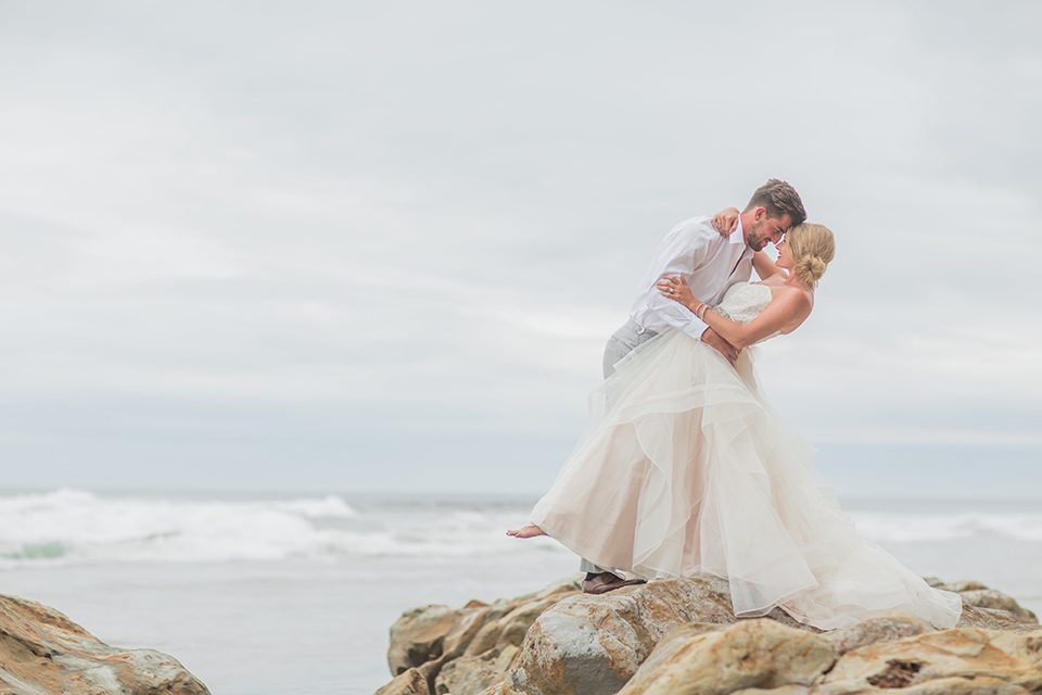 San diego beach wedding at blacks beach bride strapless ball gown with a sweetheart neckline and crystal belt and headband with groom light grey peak lapel suit by ike behar with a matching vest and white dress shirt with a long red matte tie and red flower lapel pin standing on the rocks hugging and smiling