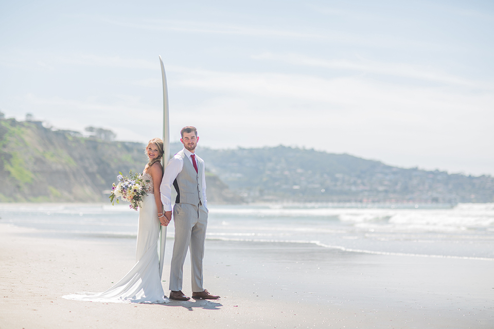 San diego beach wedding at blacks beach bride strapless ball gown with a sweetheart neckline and crystal belt and headband with groom light grey peak lapel suit by ike behar with a matching vest and white dress shirt with a long red matte tie and red flower lapel pin standing on the beach by surfboard holding hands