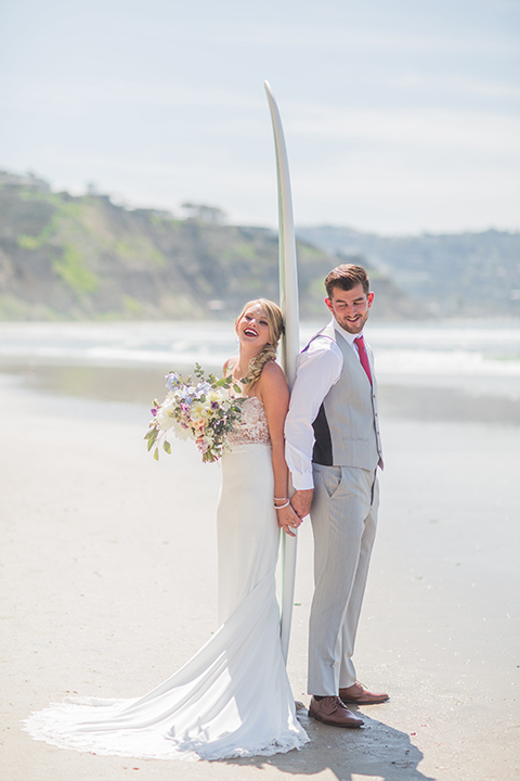 San diego beach wedding at blacks beach bride strapless ball gown with a sweetheart neckline and crystal belt and headband with groom light grey peak lapel suit by ike behar with a matching vest and white dress shirt with a long red matte tie and red flower lapel pin standing on the beach with surfboard holding hands and smiling