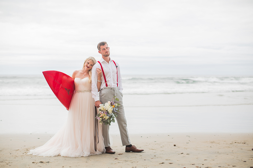 San diego beach wedding at blacks beach bride strapless ball gown with a sweetheart neckline and crystal belt and headband with groom light grey peak lapel suit by ike behar with a matching vest and white dress shirt with a long red matte tie and red flower lapel pin standing on the beach bride holding red surfboard and groom holding pink and blue floral bridal bouquet for bride
