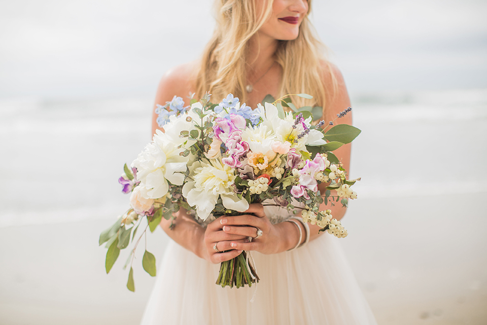 San diego beach wedding at blacks beach bride strapless ball gown with a sweetheart neckline and crystal belt and headband holding light pink and blue floral bridal bouquet close up on bouquet