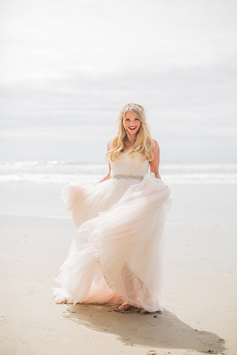 San diego beach wedding at blacks beach bride strapless ball gown with a sweetheart neckline and crystal belt and headband holding dress and walking on the beach
