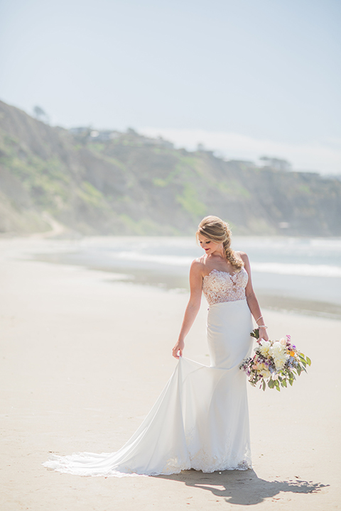 San diego beach wedding at blacks beach bride strapless ball gown with a sweetheart neckline and crystal belt and headband holding dress and light pink and blue floral bridal bouquet looking down at dress