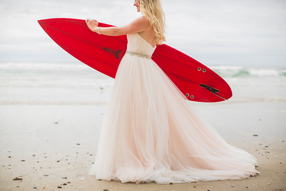 San diego beach wedding at blacks beach bride strapless ball gown with a sweetheart neckline and crystal belt and headband holding red surfboard under arm standing on the beach close up