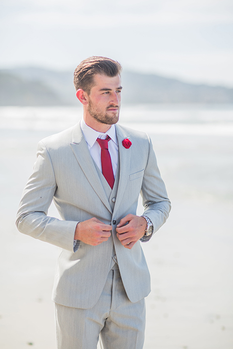 San diego beach wedding at blacks beach groom light grey peak lapel suit by ike behar with a matching vest and white dress shirt with a long red matte tie and matching red flower lapel pin buttoning coat in the front