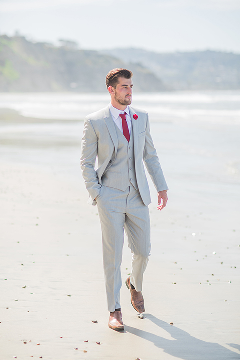 San diego beach wedding at blacks beach groom light grey peak lapel suit by ike behar with a matching vest and white dress shirt with a long red matte tie and matching red flower lapel pin walking on the beach with hand in pocket