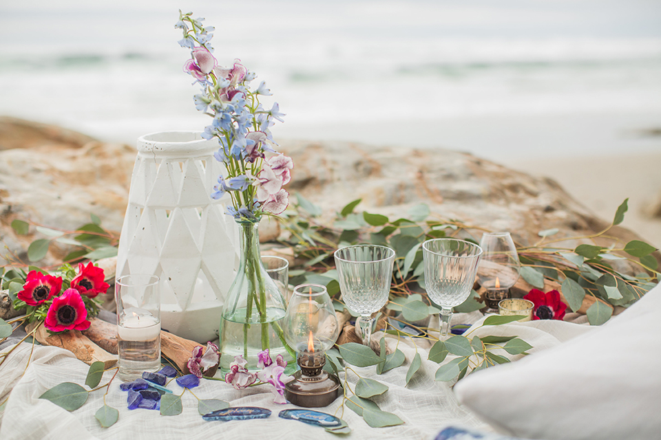 San diego beach wedding at blacks beach white blanket set up on the sand with rocks behind and light blue decorative pillows with light blue and pink flower decor and crystal wine glasses with blue geode rock name plates for bride and groom in calligraphy writing wedding photo idea for beach blanket set up