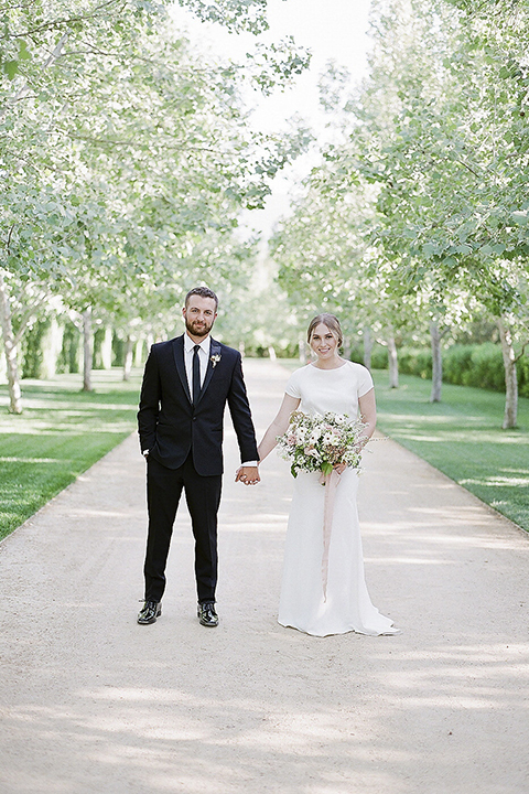 Santa barbara outdoor black tie wedding at kestrel park bride simple form fitting gown with a high neckline and short sleeves and groom black peak lapel tuxedo and a white dress shirt with a long black skinny tie and green floral boutonniere holding hands and bride holding white and green floral bridal bouquet