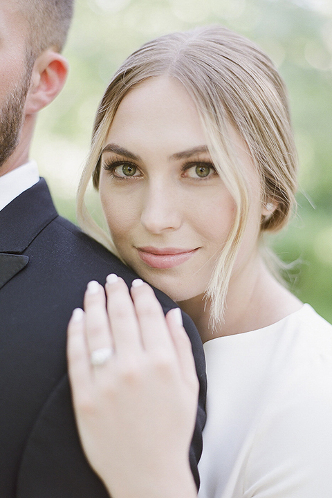 Santa barbara outdoor black tie wedding at kestrel park bride simple form fitting gown with a high neckline and short sleeves and groom black peak lapel tuxedo and a white dress shirt with a long black skinny tie and green floral boutonniere hugging bride behind groom close up on bride