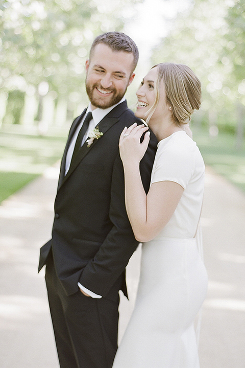 Santa barbara outdoor black tie wedding at kestrel park bride simple form fitting gown with a high neckline and short sleeves and groom black peak lapel tuxedo and a white dress shirt with a long black skinny tie and green floral boutonniere hugging bride behind groom smiling