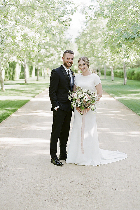 Santa barbara outdoor black tie wedding at kestrel park bride simple form fitting gown with a high neckline and short sleeves and groom black peak lapel tuxedo and a white dress shirt with a long black skinny tie and green floral boutonniere hugging and smiling bride holding white and green floral bridal bouquet