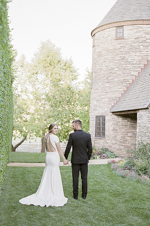 Santa barbara outdoor black tie wedding at kestrel park bride simple form fitting gown with a high neckline and short sleeves and groom black peak lapel tuxedo and a white dress shirt with a long black skinny tie and green floral boutonniere holding hands far away back view