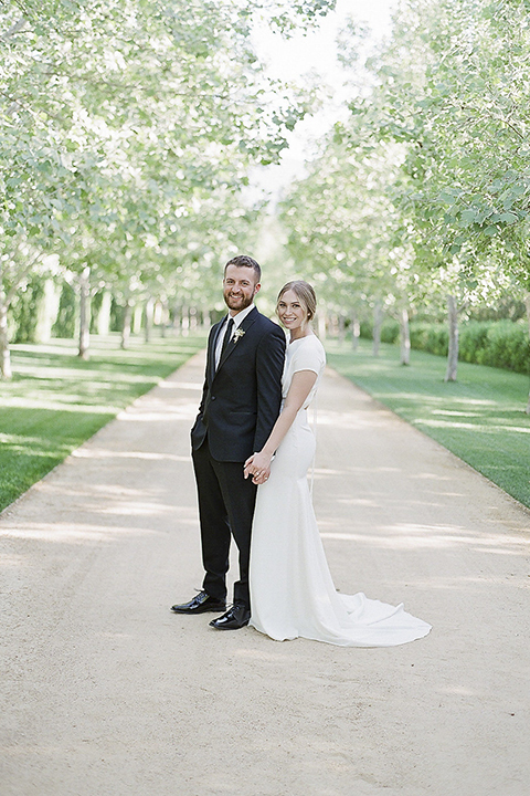 Santa barbara outdoor black tie wedding at kestrel park bride simple form fitting gown with a high neckline and short sleeves and groom black peak lapel tuxedo and a white dress shirt with a long black skinny tie and green floral boutonniere holding hands bride behind groom smiling