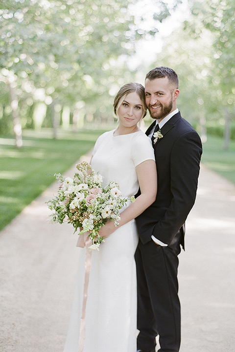 Santa barbara outdoor black tie wedding at kestrel park bride simple form fitting gown with a high neckline and short sleeves and groom black peak lapel tuxedo and a white dress shirt with a long black skinny tie and green floral boutonniere hugging and bride holding white and green floral bridal bouquet
