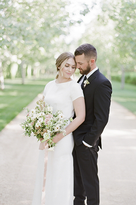 Santa barbara outdoor black tie wedding at kestrel park bride simple form fitting gown with a high neckline and short sleeves and groom black peak lapel tuxedo and a white dress shirt with a long black skinny tie and green floral boutonniere hugging and touching heads bride holding white and green floral bridal bouquet