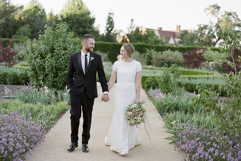 Santa barbara outdoor black tie wedding at kestrel park bride simple form fitting gown with a high neckline and short sleeves and groom black peak lapel tuxedo and a white dress shirt with a long black skinny tie and green floral boutonniere walking and holding hands bride holding white and green floral bridal bouquet