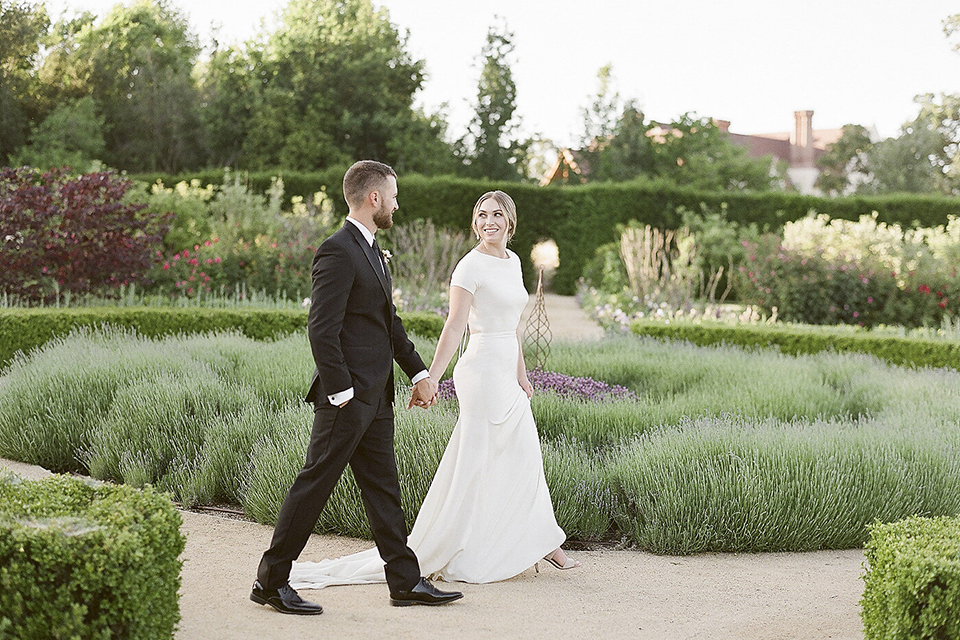 Santa barbara outdoor black tie wedding at kestrel park bride simple form fitting gown with a high neckline and short sleeves and groom black peak lapel tuxedo and a white dress shirt with a long black skinny tie and green floral boutonniere holding hands and walking and bride holding white and green floral bridal bouquet