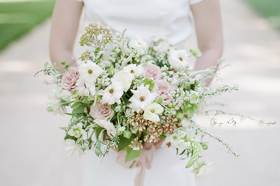 Santa barbara outdoor black tie wedding at kestrel park bride simple form fitting gown with a high neckline and short sleeves holding white and green floral bridal bouquet close up on bouquet