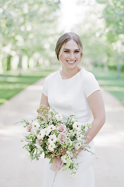 Santa barbara outdoor black tie wedding at kestrel park bride simple form fitting gown with a high neckline and short sleeves holding white and green floral bridal bouquet smiling