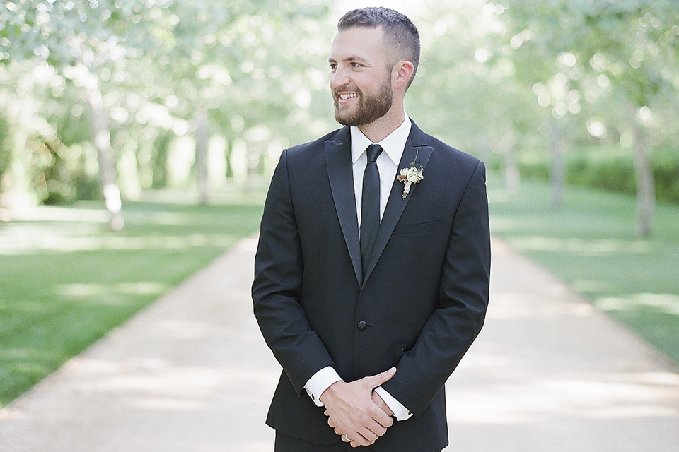 Santa barbara outdoor black tie wedding at kestrel park groom black peak lapel tuxedo with a white dress shirt and long black skinny tie with a green floral boutonniere standing with hands crossed in front smiling close up