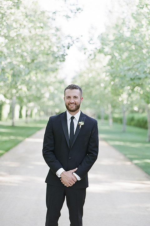 Santa barbara outdoor black tie wedding at kestrel park groom black peak lapel tuxedo with a white dress shirt and long black skinny tie with a green floral boutonniere standing with hands crossed in front smiling