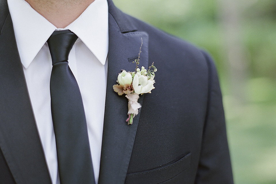 Santa barbara outdoor black tie wedding at kestrel park groom black peak lapel tuxedo with a white dress shirt and long black skinny tie with a green floral boutonniere close up