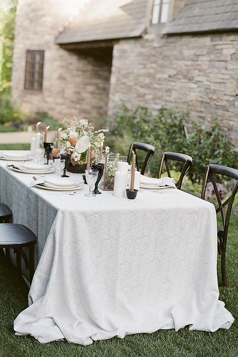 Santa barbara outdoor black tie wedding at kestrel park table set up with white lace linen and white place settings with white linen napkins and black wine glasses with white and green floral centerpiece decor with black and gold candles and wooden rustic chairs
