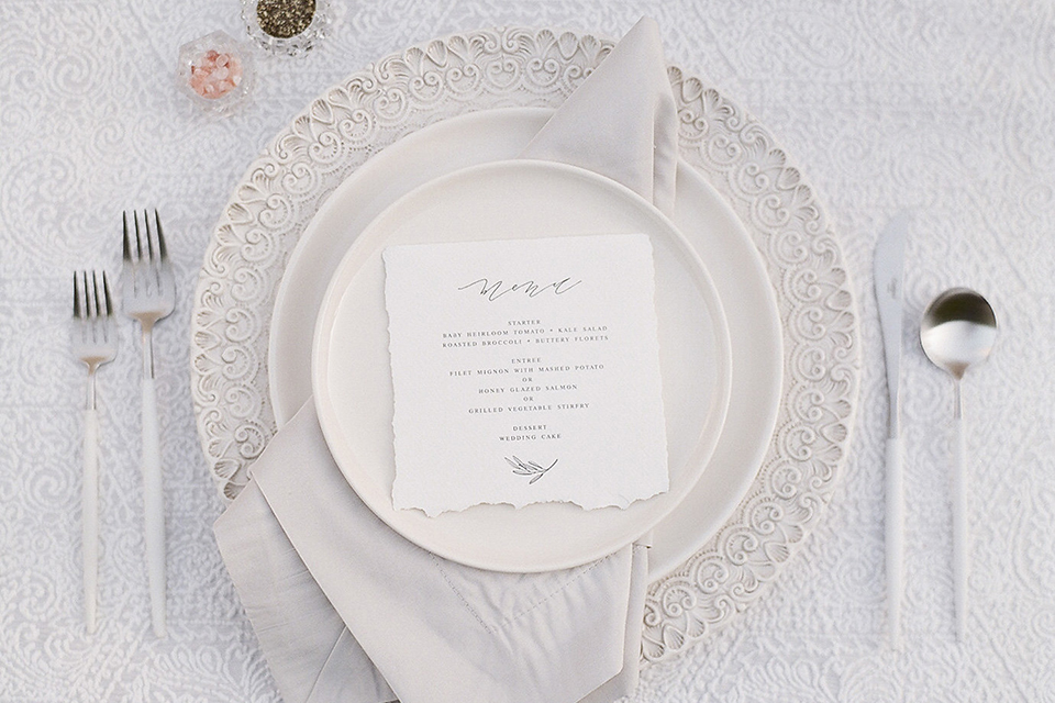 Santa barbara outdoor black tie wedding at kestrel park table set up with white lace linen and white place settings with white linen napkins and black wine glasses with white and green floral centerpiece decor with black and gold candles and wooden rustic chairs close up on place setting