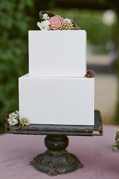 Santa barbara outdoor black tie wedding at kestrel park two tier white wedding cake square shaped on black cake tray with greenery floral decor on bottom and on top with dusty pink linen decor on table wedding photo idea for cake