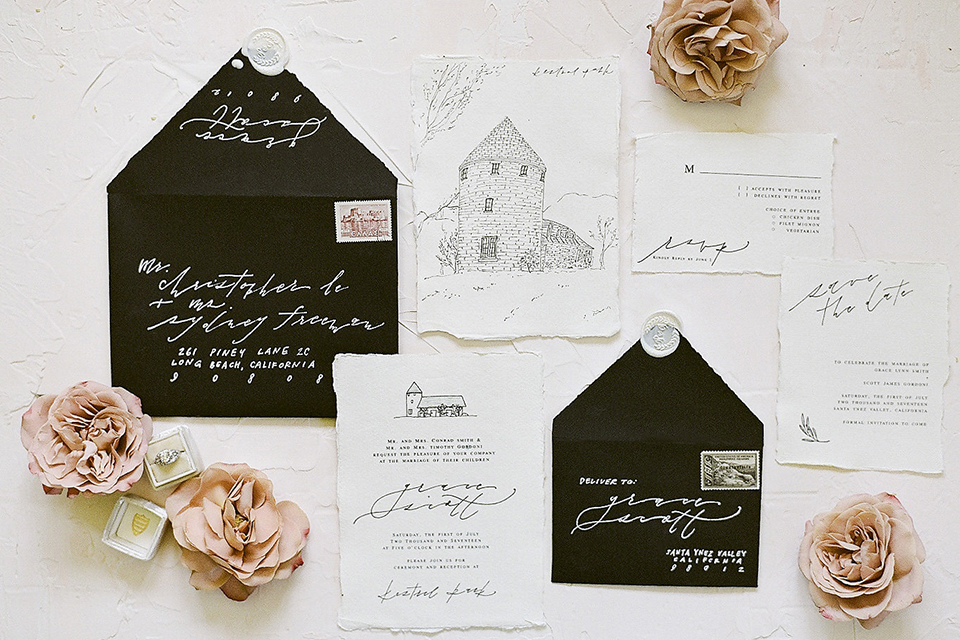 Santa barbara outdoor black tie wedding at kestrel park white background with black and white wedding invitations with black envelopes and white invitations with black calligraphy writing and drawing of venue with light pink flower decor on ground next to invitations wedding photo idea for invitations