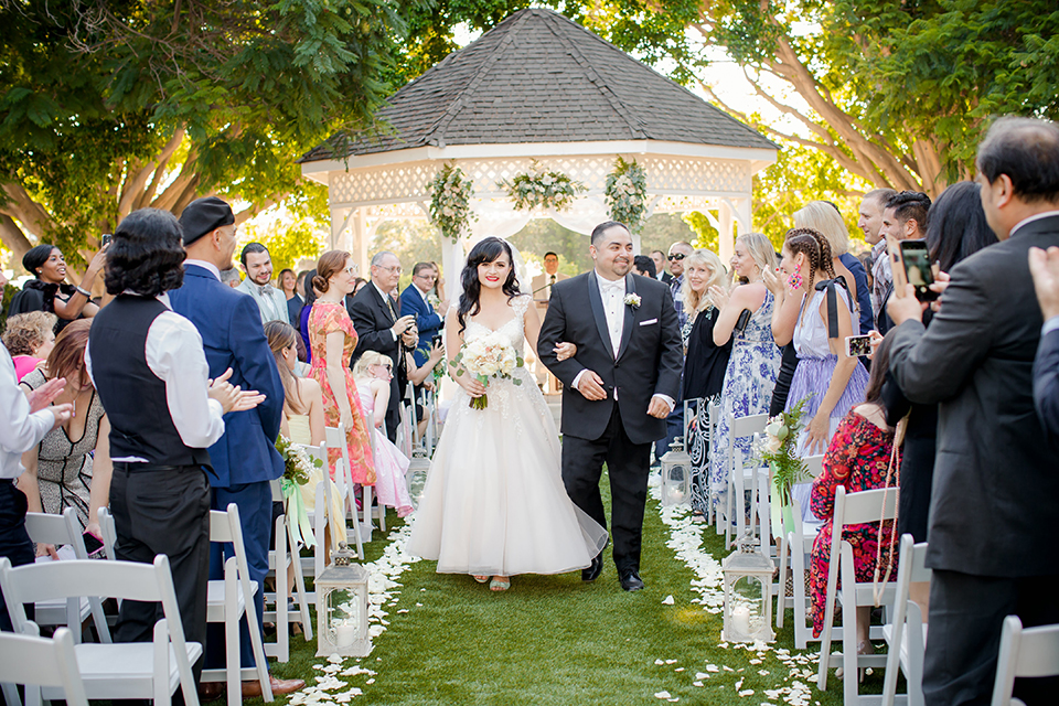 Orange county outdoor summer wedding at the heritage museum bride ball gown with lace straps and a sweetheart neckline with a short tulle skirt and long veil with groom black shawl lapel tuxedo with a white dress shirt and white vest with a white tie and white floral boutonniere holding hands and walking down the aisle after ceremony bride holding white floral bridal bouquet