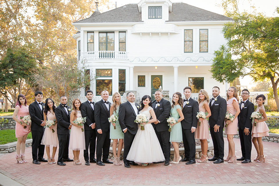 Orange county outdoor summer wedding at the heritage museum bride ball gown with lace straps and a sweetheart neckline with a short tulle skirt and long veil with groom black shawl lapel tuxedo with a white dress shirt and white vest with a white tie and white floral boutonniere standing with wedding party