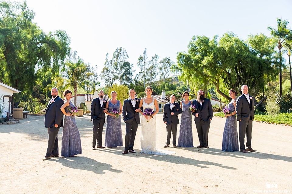 San diego outdoor wedding at leo carillo ranch bride form fitting gown with a sweetheart neckline with thin straps and beaded detail on bodice with groom charcoal grey tuxedo with a black shawl and matching vest with a white dress shirt and plaid bow tie with a white floral boutonniere standing with wedding party groomsmen charcoal grey tuxedos and bridesmaids long dusty blue beaded dresses