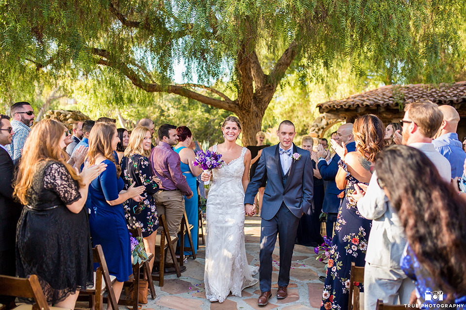 San diego outdoor wedding at leo carillo ranch bride form fitting gown with a sweetheart neckline with thin straps and beaded detail on bodice with groom charcoal grey tuxedo with a black shawl and matching vest with a white dress shirt and plaid bow tie with a white floral boutonniere walking down the aisle after ceremony holding hands and smiling