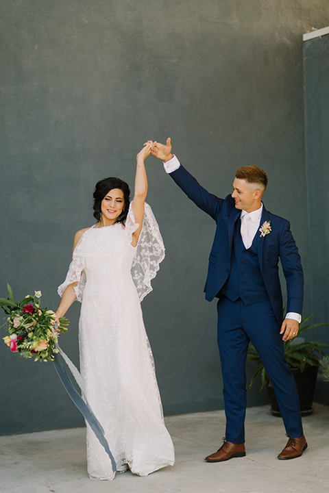 Los angeles outdoor colorful wedding bride a line gown with a high neckline and open shoulder lace sleeves and groom cobalt blue notch lapel suit by allure men with a matching vest and white dress shirt with a long white matte tie and white floral boutonniere dancing and twirling bride