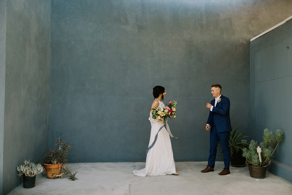 Los angeles outdoor colorful wedding bride a line gown with a high neckline and open shoulder lace sleeves and groom cobalt blue notch lapel suit by allure men with a matching vest and white dress shirt with a long white matte tie and white floral boutonniere first look groom smiling