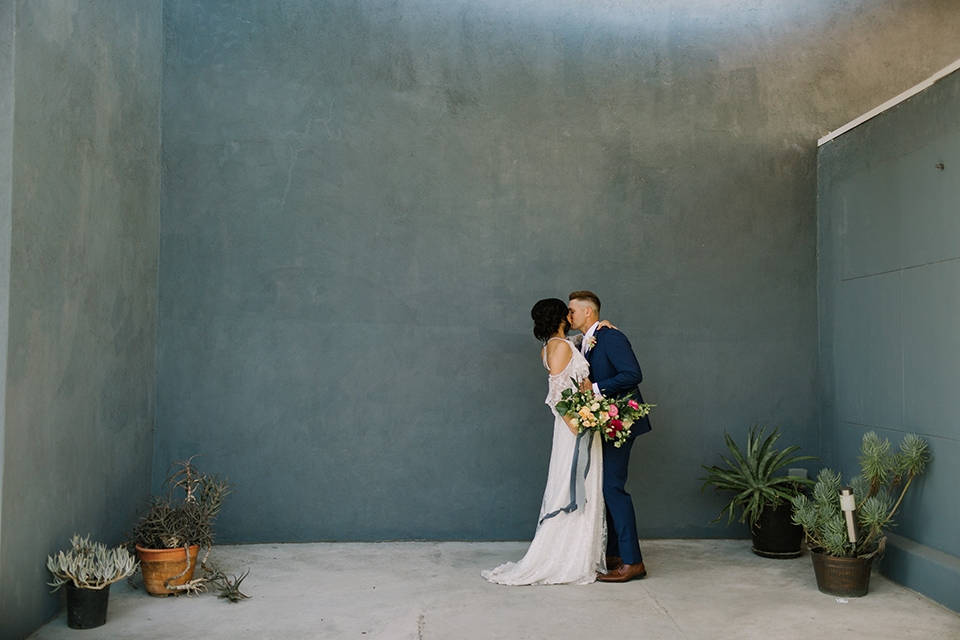 Los angeles outdoor colorful wedding bride a line gown with a high neckline and open shoulder lace sleeves and groom cobalt blue notch lapel suit by allure men with a matching vest and white dress shirt with a long white matte tie and white floral boutonniere first look bride and groom kissing