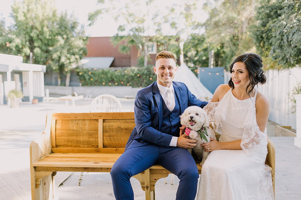Los angeles outdoor colorful wedding bride a line gown with a high neckline and open shoulder lace sleeves and groom cobalt blue notch lapel suit by allure men with a matching vest and white dress shirt with a long white matte tie and white floral boutonniere sitting on wooden bench with dog smiling