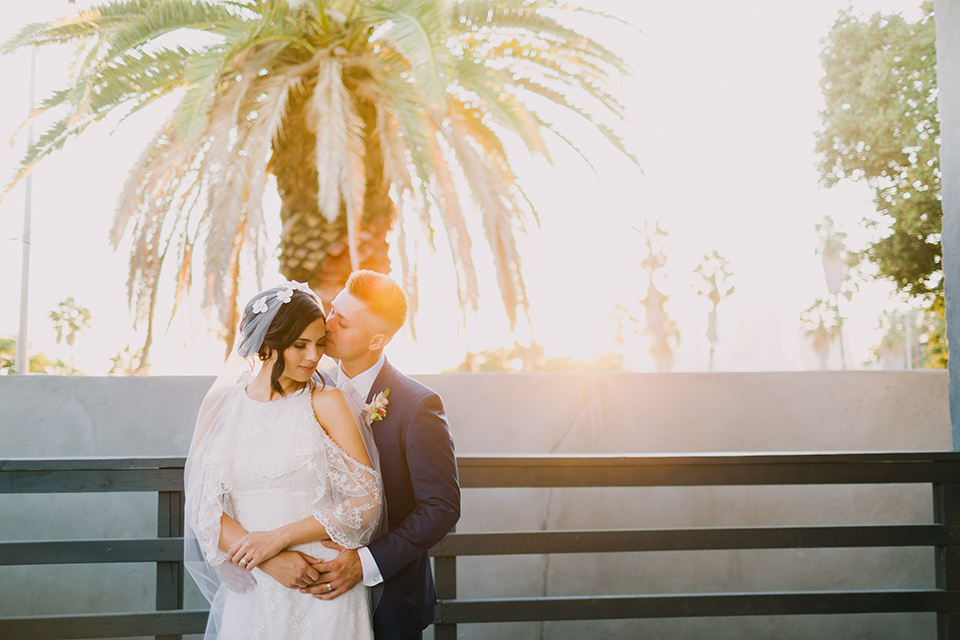 Los angeles outdoor colorful wedding bride a line gown with a high neckline and open shoulder lace sleeves and groom cobalt blue notch lapel suit by allure men with a matching vest and white dress shirt with a long white matte tie and white floral boutonniere standing and hugging sunset