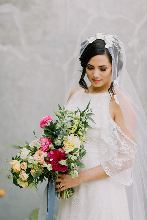 Los angeles outdoor colorful wedding bride a line gown with a high neckline and open shoulder lace sleeves with long veil and lace detail holding colorful floral bridal bouquet with long blue ribbon close up